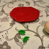 Modele uma bola com a massa branca, um círculo achatado com a vermelha e faça folhinhas com a verde. Precisaremos, ainda, de grãos de gergelim preto e de cravos.